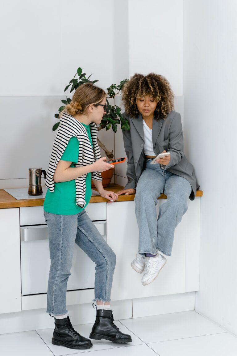 foto-duas-mulheres-uma-branca-uma-preta-na-cozinha-olhando-seus-celulares